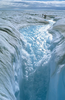 A stream of melt water cascading off the vast Arctic ice sheet which covers Greenland. The ice sheet is melting because of global warming. Roger Braithwaite/Peter Arnold, Inc.