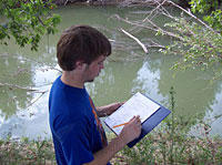 Young man standing near river writing in a notebook.