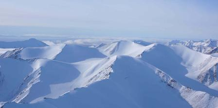 Panoramic expanse of snow-covered mountains in the Arctic.