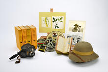 Memorabilia from an early 20th-century expedition, including field sketches, books, film reels, photographs, and pith helmet.