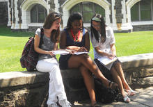 Three teenagers sit on a low stone wall on a grassy campus and compare paper handouts with each other.