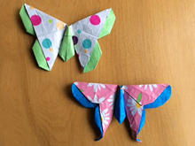 Two butterfly models created from folded paper lie on a wood-grained surface.