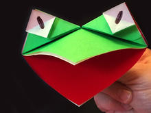Hand holds a puppet created from folded paper, shaped to resemble a frog.