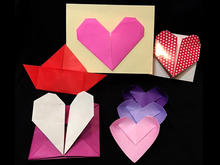 Seven colorful hearts crafted from folder paper.