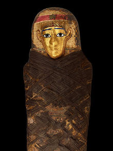 Detail view of the layers of the headdress of the Gilded Lady mummy, made from papyrus and linen, topped with a gold-painted face.