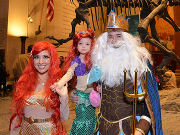 A child wear an Ariel the Mermaid costume, accompanied by two adults dressed as a mermaid and King Neptune.