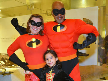 "Two adults and one child are dressed in costume as characters from ""The Incredibles"" movie."