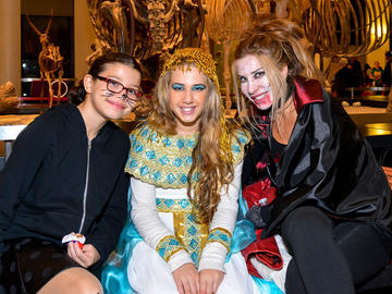 Three teenagers are dressed in costumes as a cat, a goddess and a vampire.