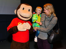 A person wearing a Curious George costume stands next to a woman holding a child.