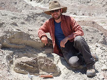 Zac smiles and wears a hat and sunglasses as he sits on the desert sand, his pick-axe on the ground nearby.