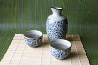 Blue and white ceramic sake carafe with two matching cups on a bamboo mat