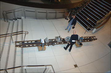 Overhead of people around a large girder, an interferometer used as a tool in astronomy