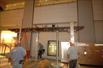 Three workers face the interferometer platform during installation.