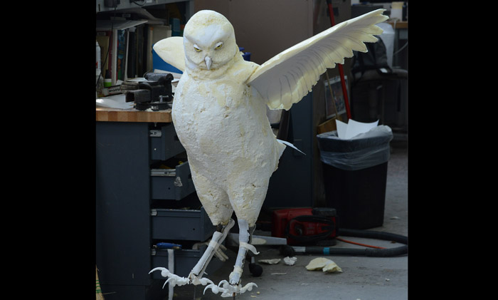 Partially completed owl model stands on the floor in the exhibit construction area.