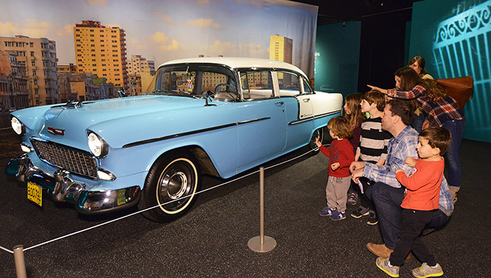 A group of adults and children look and point at a vintage '50s car parked in the Museum, placed against a photo backdrop of Havana.