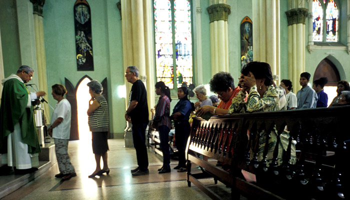 Line of people waiting to receive communion, stained glass windows in background.
