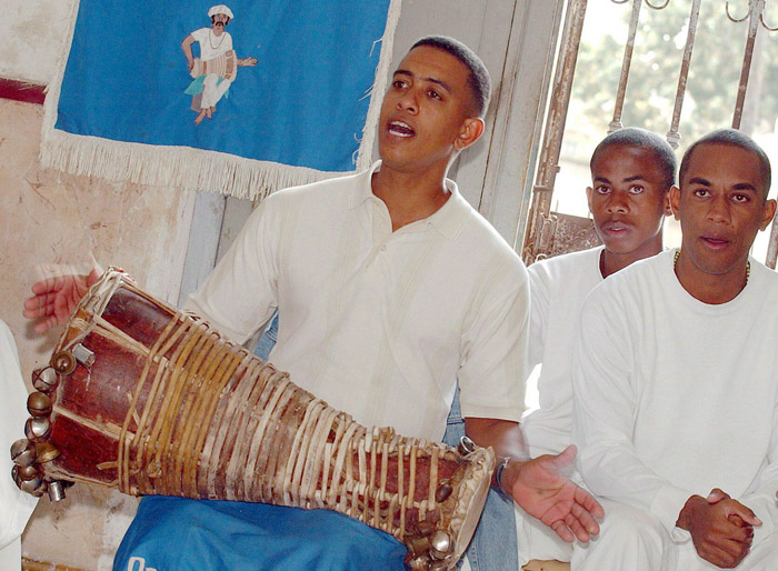Man holds a batá drum and chants while two other worshippers stand nearby.