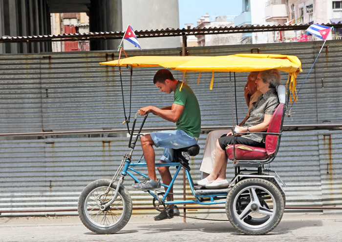 A young man pedals his bicitaxi and  transports two passengers.