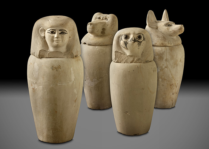 Four stone jars, the lids of which are shaped differently—one of which takes the form of a jackal, and the others represent a baboon, hawk, and human.