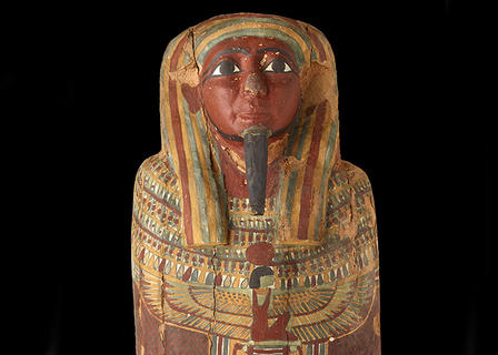 Detail of the head of the coffin shows a painted face with a long slim beard, wearing a headdress, with illustrated figures decorating the body.