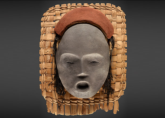 Clay mask with simply executed closed eyes, slim nose and open mouth rests atop a straw mat.