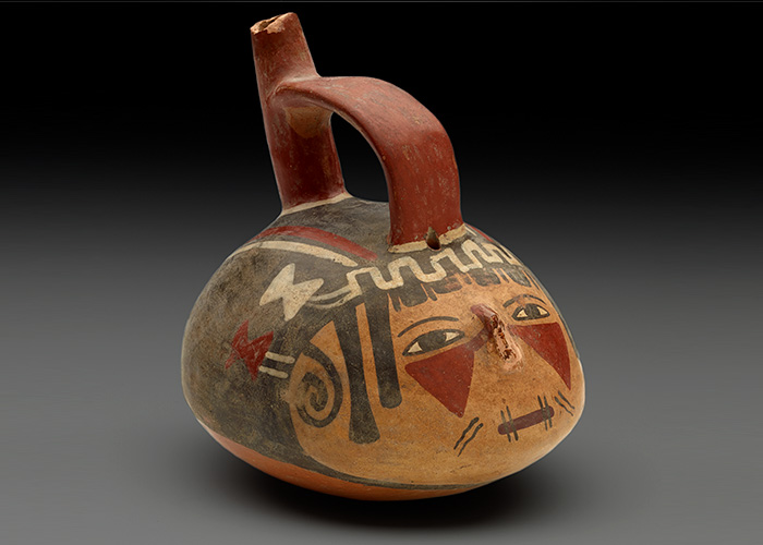 Rounded vessel in the shape of a human head has a face painted on it and is fitted with a handle and spout.