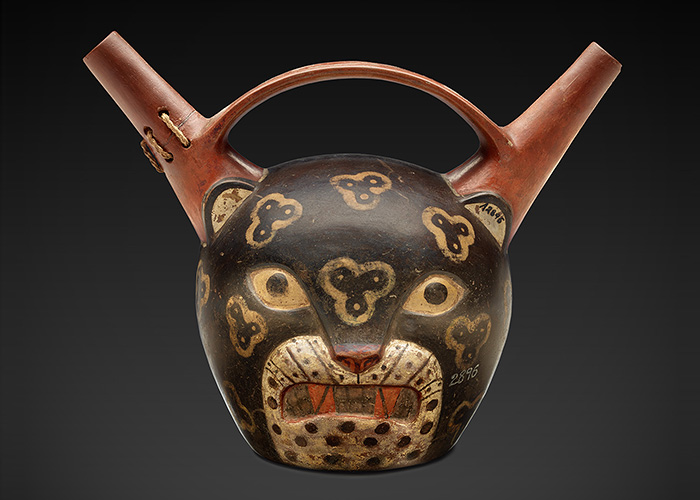 Ceramic jar is shaped and painted like the head of a jaguar with ears that are extended into spouts on either side of a handle.