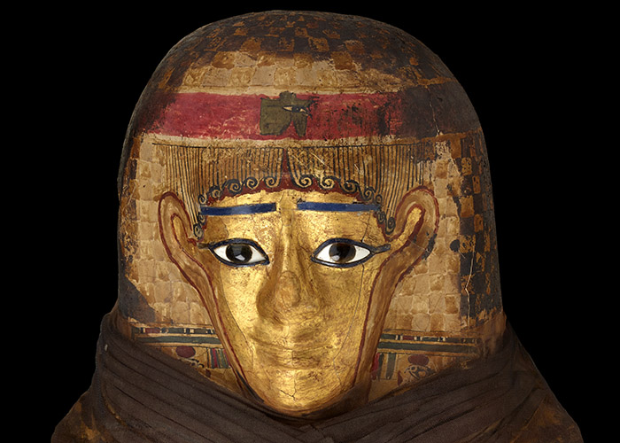 Detail view of the layers of the headdress made from papyrus and linen, topped with a gold-painted face.