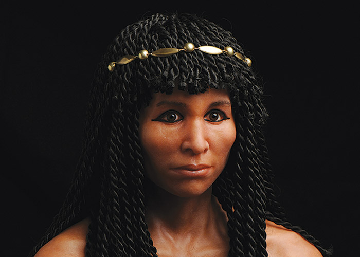 Realistic sculpture of the head and shoulders of a woman, featuring kohl-rimmed eyes, shoulder length braided hair with bangs and a gold circlet.