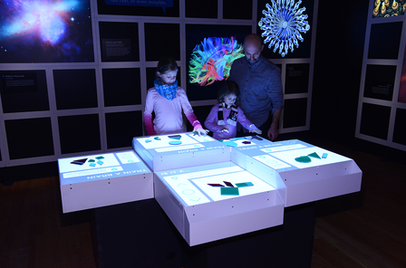Children and adults gather around four lit tabletop surfaces that hold that plastic shapes.