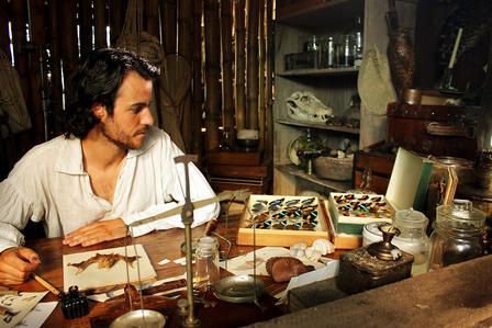 Man sits at a work table holding bat and butterfly and other specimens.