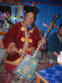 An older man in traditional clothes kneels on the floor with a stringed instrument and bow.
