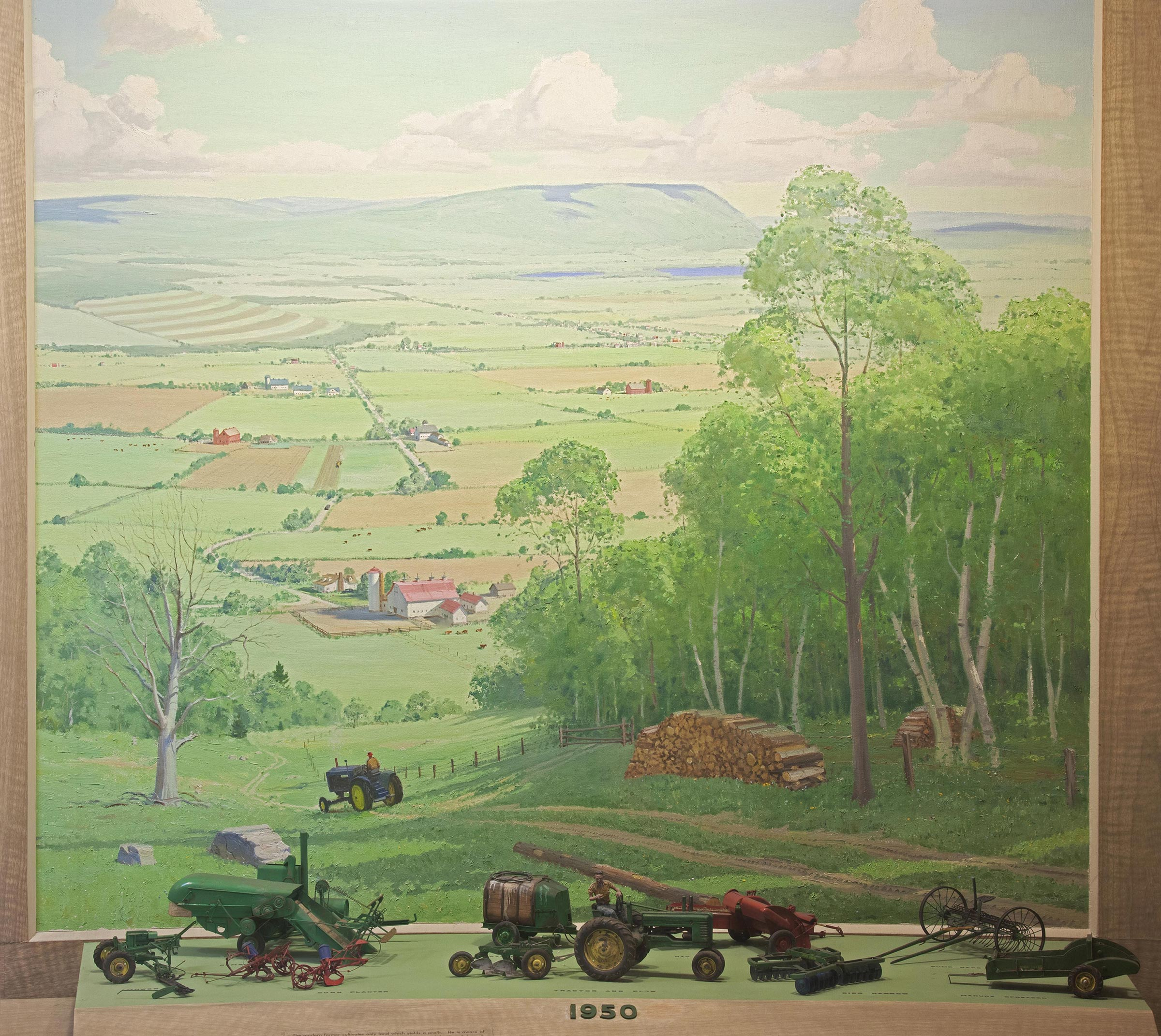 Scale models of farming tools from 1950 with background painting of a landscape with a farm.