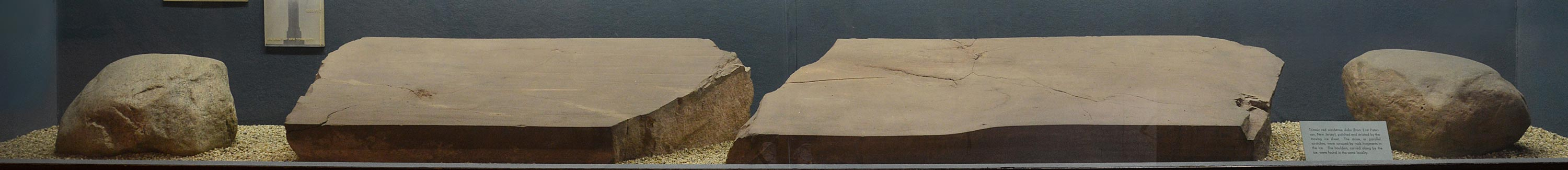 Bottom of museum case showing four pieces of red sandstone slabs.