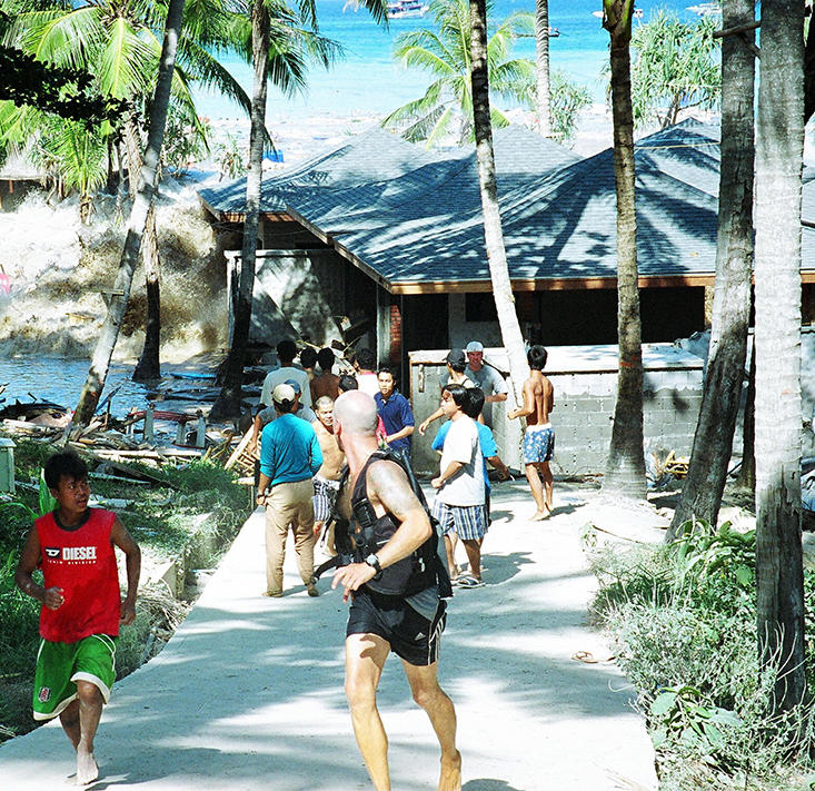 "People fleeing as a tsunami wave comes crashing ashore on December 26, 2004, at Koh Raya, part of Thailand's territory in the Andaman Islands. The photographer who took this picture escaped without injury but retreated at the first wave and watched as a second wave tore apart the wooden buildings, with a third and largest wave coming forward and ""ripping apart the cement buildings like they were made of balsa wood."" © John Russell/AFP/Getty Images"