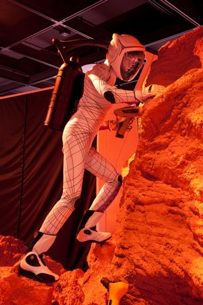 In the Mars diorama, an astronaut wearing a pressurized BioSuit™ designed by MIT Professor Dava Newman climbs a Martian rock formation. © AMNH/D. Finnin