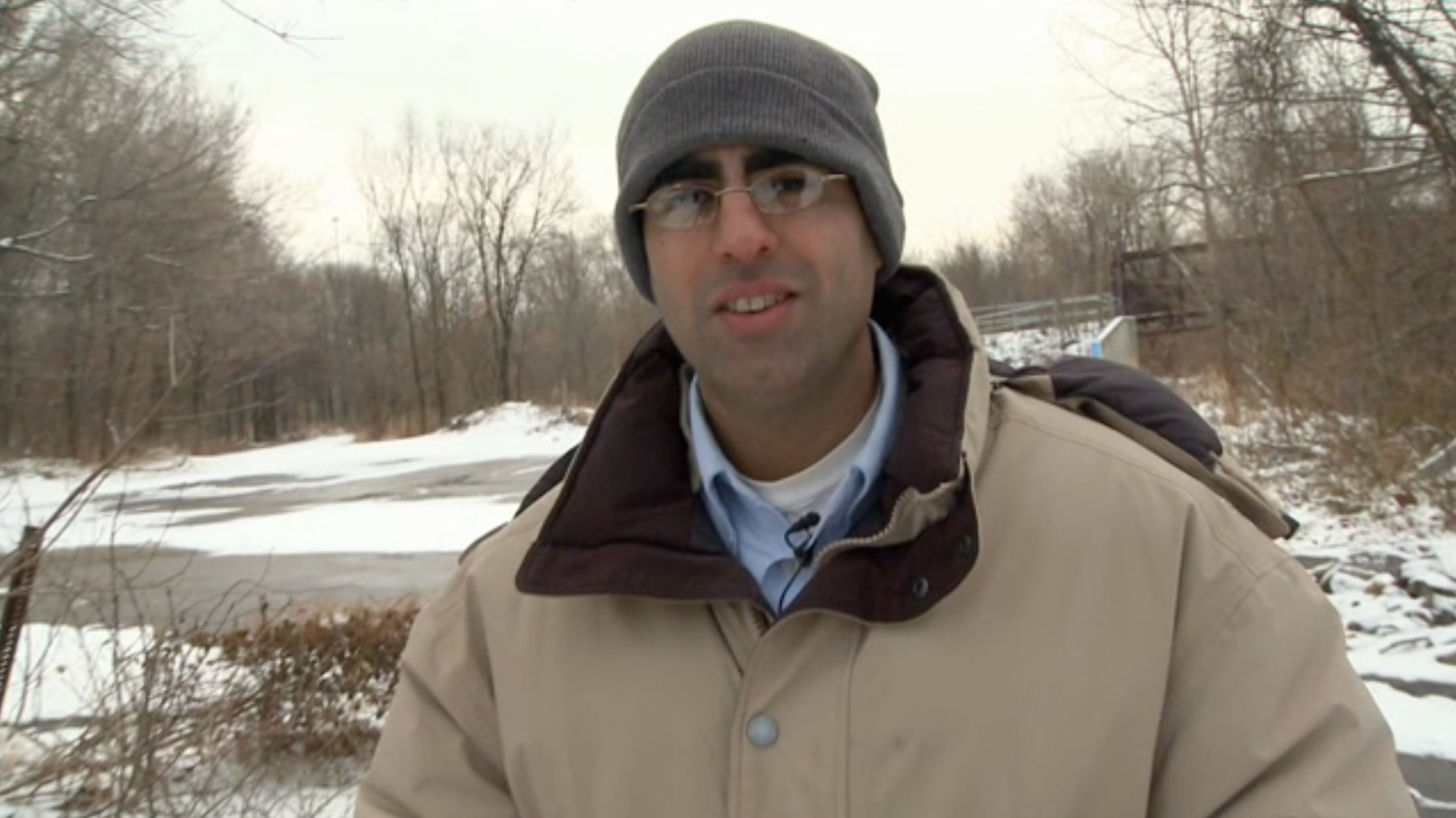 A man, scientist Sujay Kaushal, wearing a knit hat, jacket, and lavalier microphone on shirt collar outside in the snow, with trees in the background.