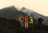 A group of people in field gear view the active volcano Mount Etna.