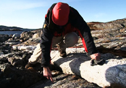 Martin Whitehouse, a zircon expert from the Swedish Museum of Natural History, hunts for zircon-containing rocks on desolate Akilia Island, Greenland. AMNH