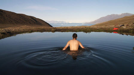A young man with short dark hair, his bare back to the camera, wades waist-deep in a remote lake in Northern Greenland, surrounded by low hills, rolling tundra, and big clear sky.