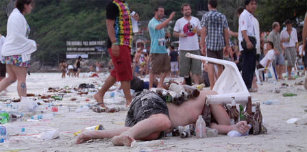 Tourist lying in trash on a beach sleeping off a night of drinking