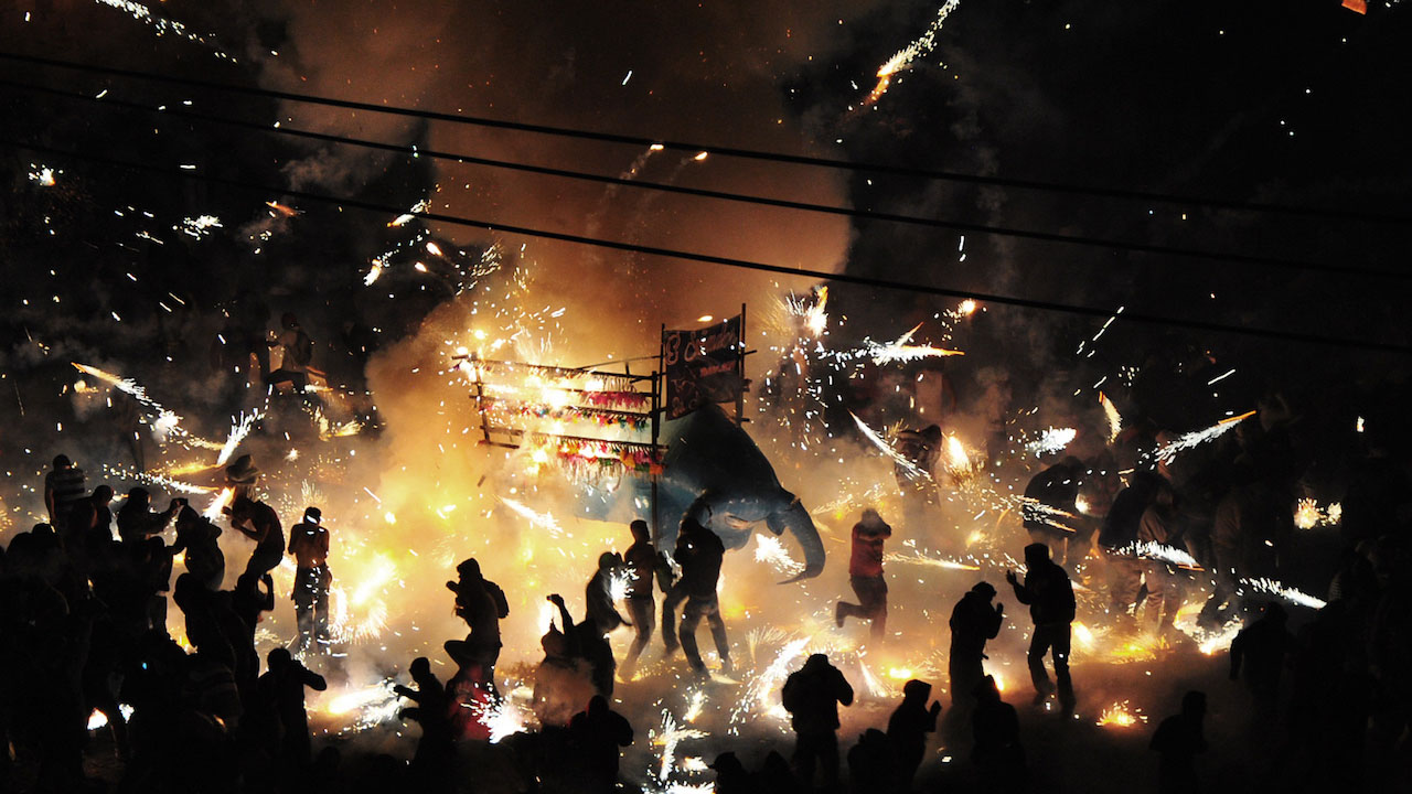 Pyrotechnics erupt throughout the darkened streets.