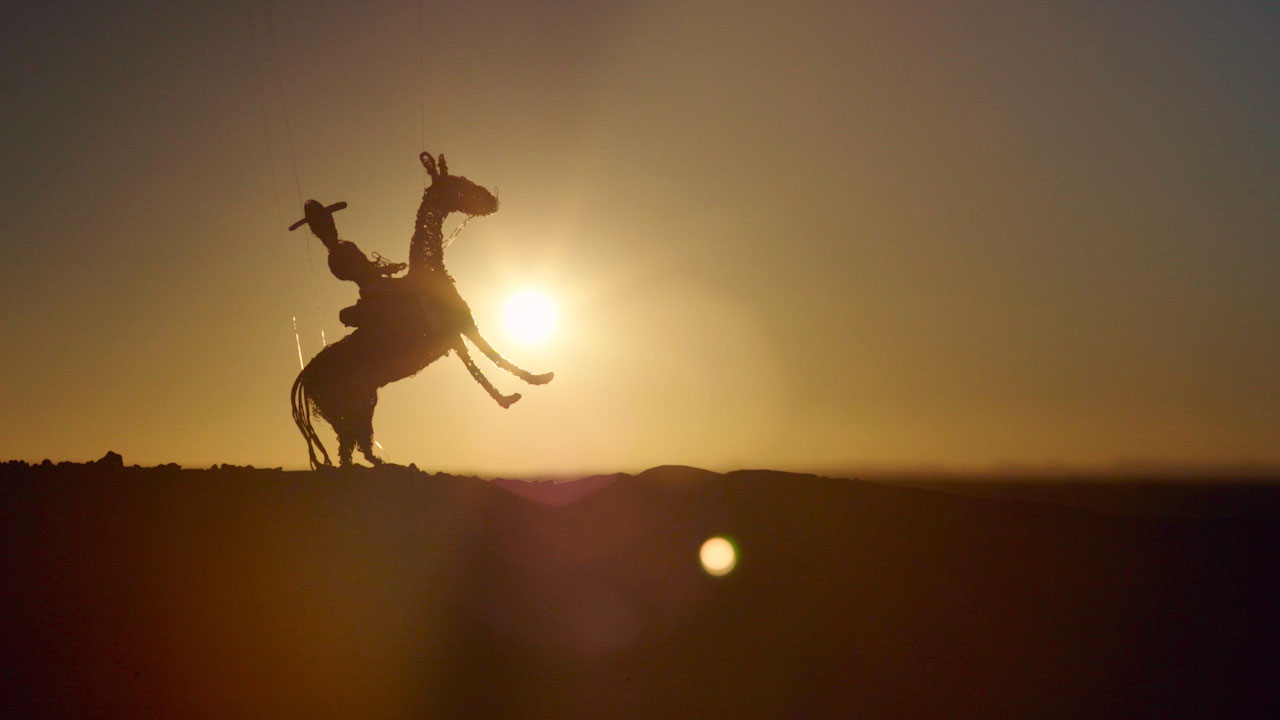 figureine of horse and rider with horse on it's hide legs on a desert with the setting sun behind them