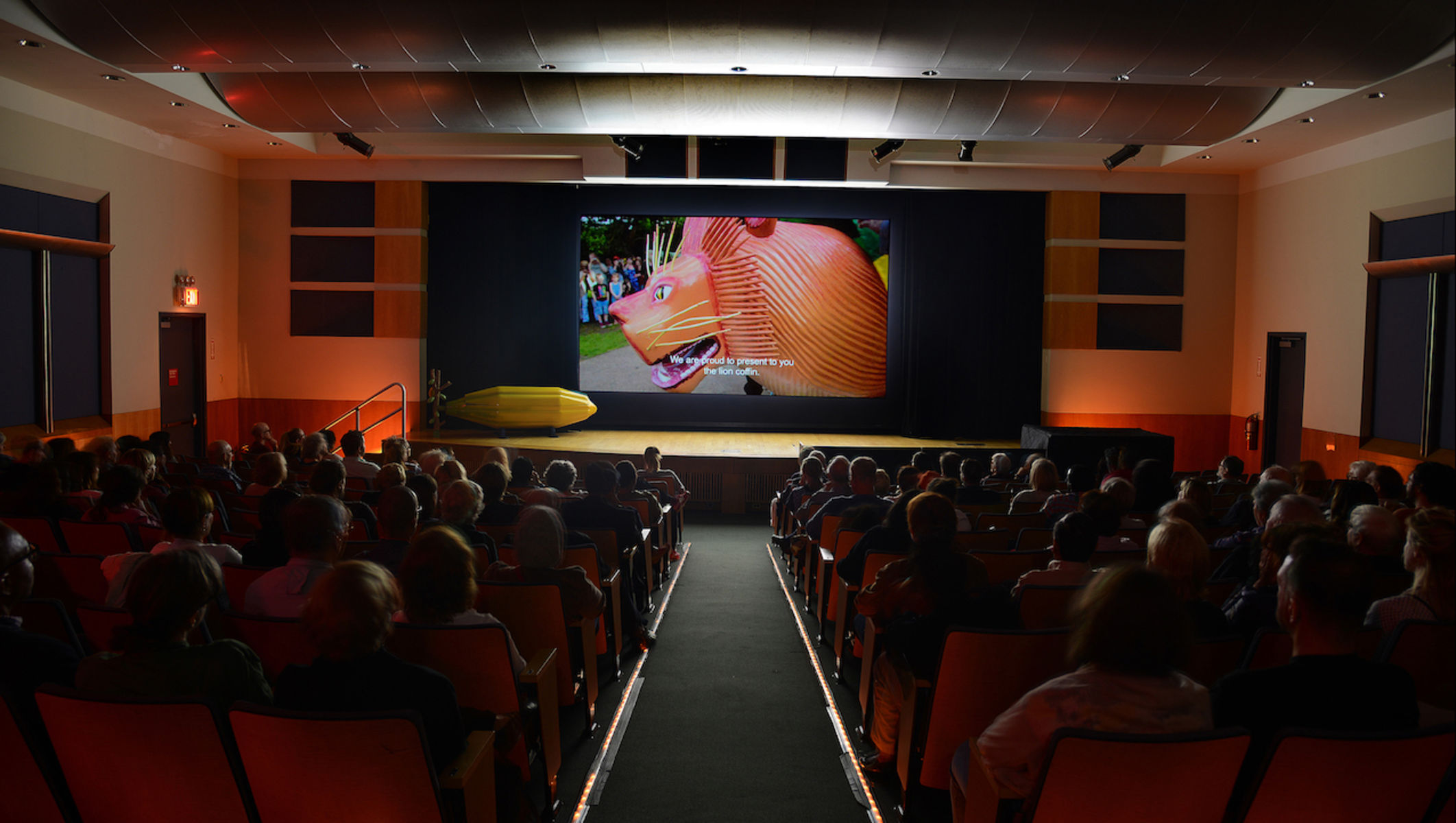 movie theater showing image of lion coffin. On the left of the stage is one of his masterpiece coffins from the Museum's anthropology collections.