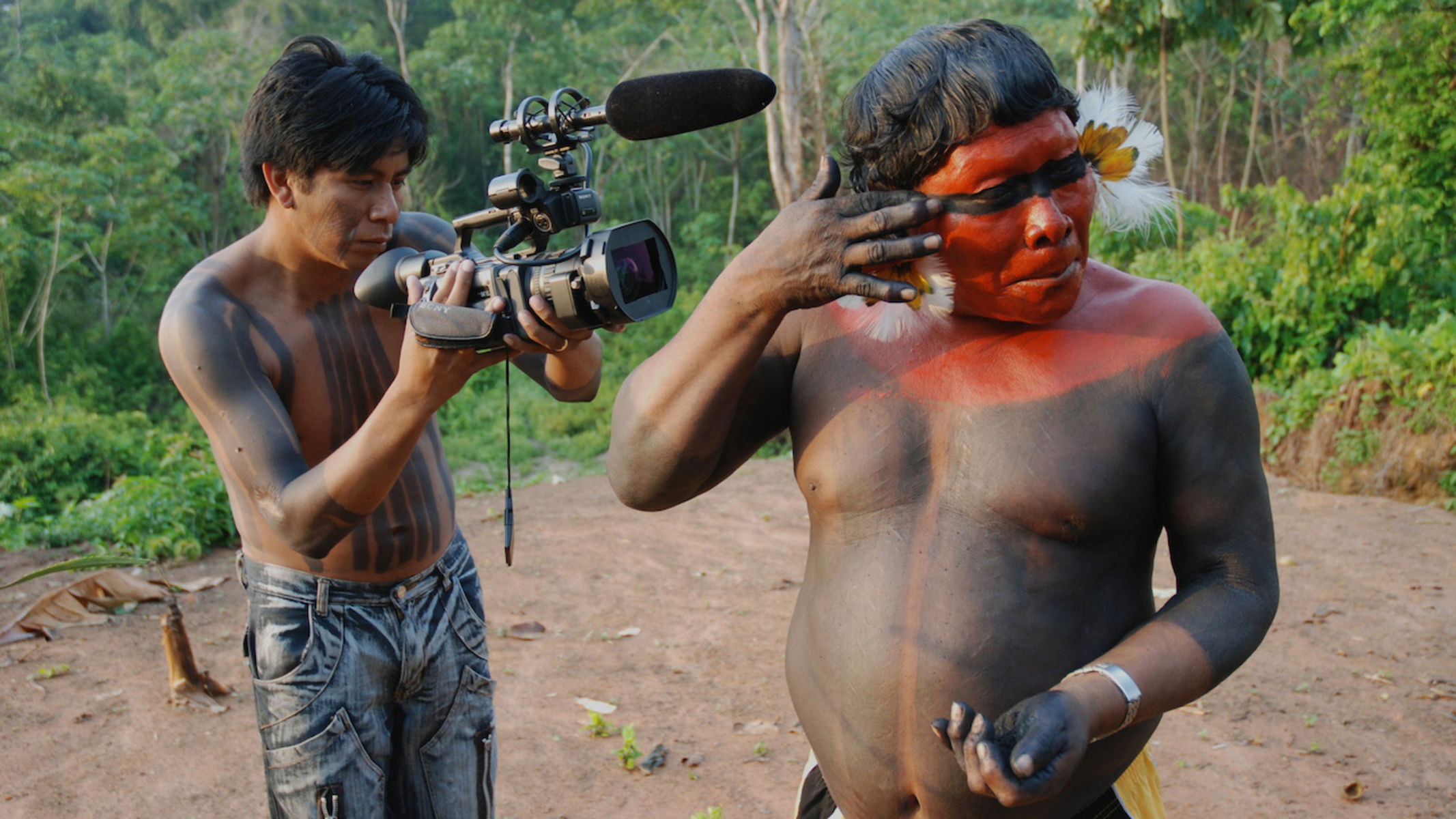 One man applies red paint to his face while another man with black paint glyphs on his chest and abdomen films closely
