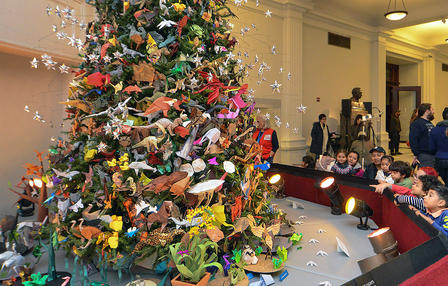 And evergreen-style tree is covered with folder paper origami models; a group of children and a few adults gather around the base of the tree.