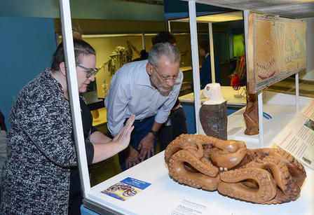 Two people examine a wood carving of an octopus and rat in an exhibit case.