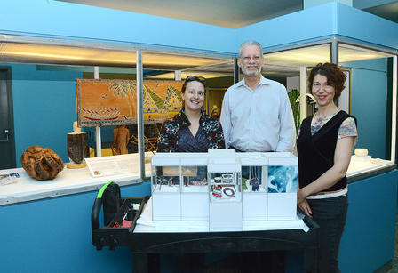 Three people stand beside a tabletop model of the new case.
