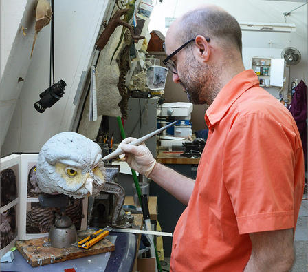 The head of the owl model is mounted on a base and Brougham uses a sculpting tool to create feathers.