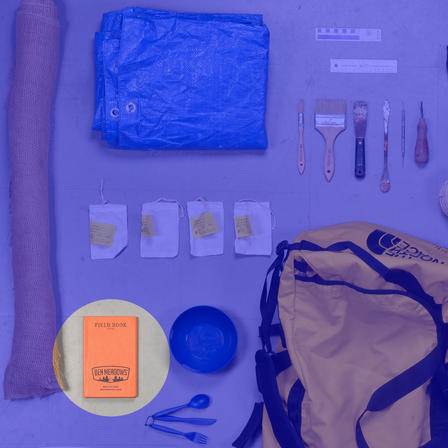 Duffle bag surrounded by tools—tarp, small labeled bags, picks and brushes, plastic bowl and utensils—field book highlighted.